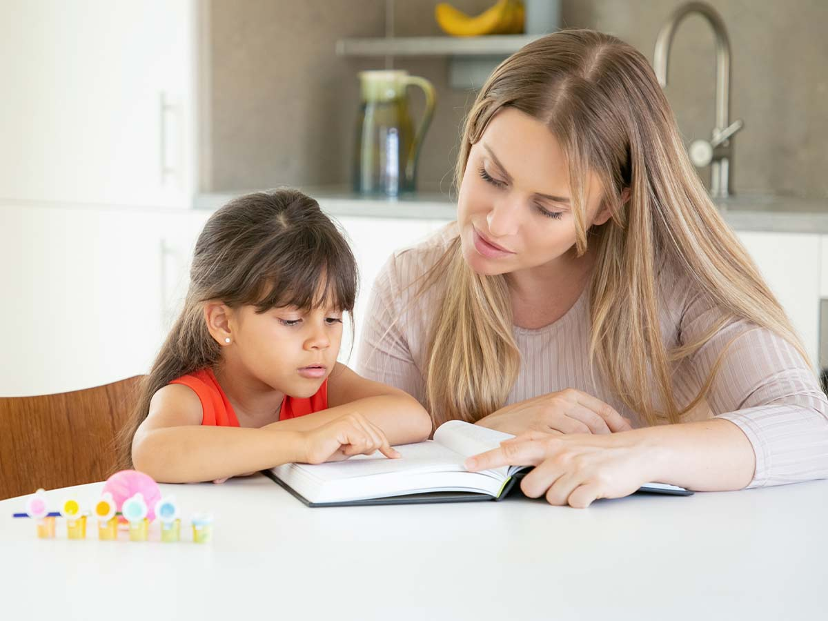 Mum and daughter sat at the kitchen table looking in a book to learn about synonyms and antonyms.
