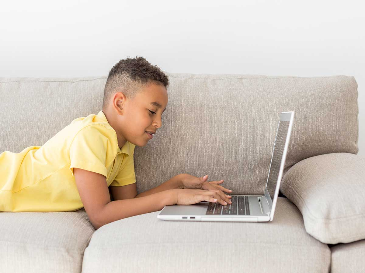 A tween boy lies on a grey sofa, he is smiling and typing on his laptop.