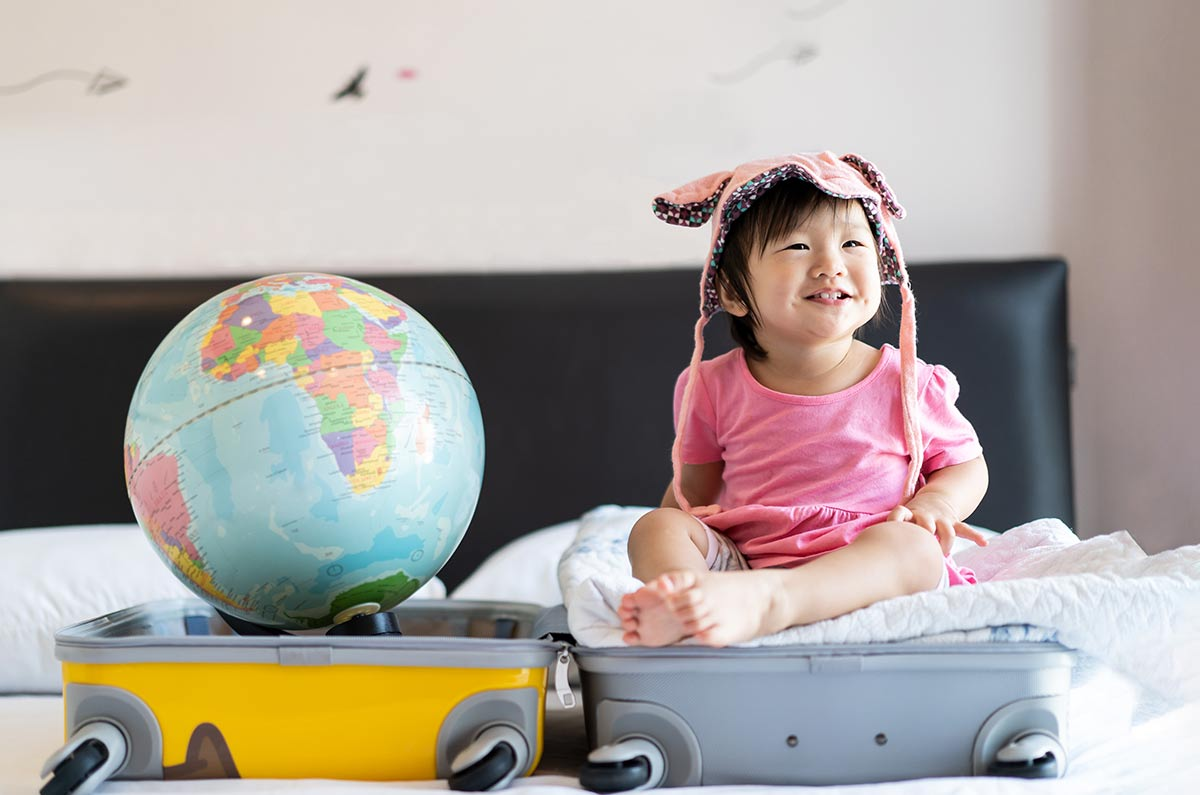 An open suitcase is on the bed, a toddler sits in one half smiling and there's a globe in the other.