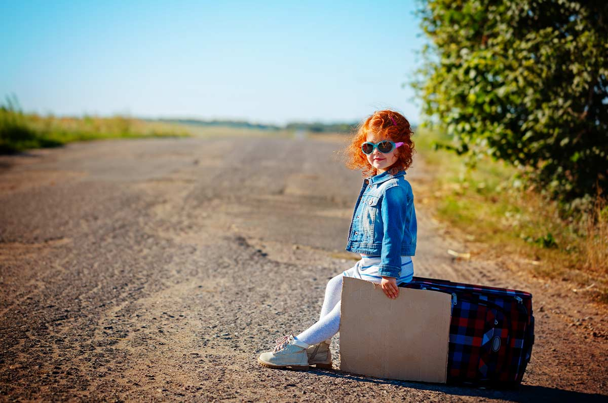 Toddler wearing sunglasses sitting on a suitcase on a country road looking happy everything has been packed for holiday.
