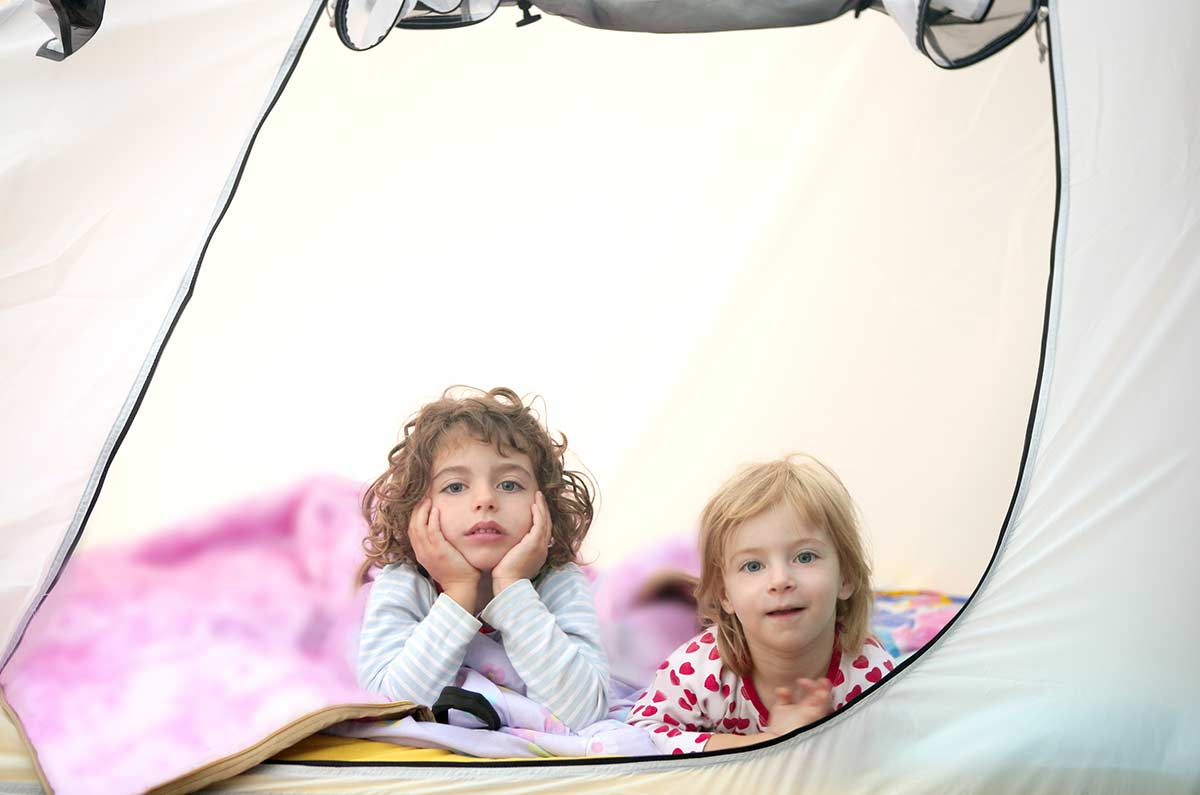Two toddlers lying on their stomachs in their camping tent looking out the zip door.