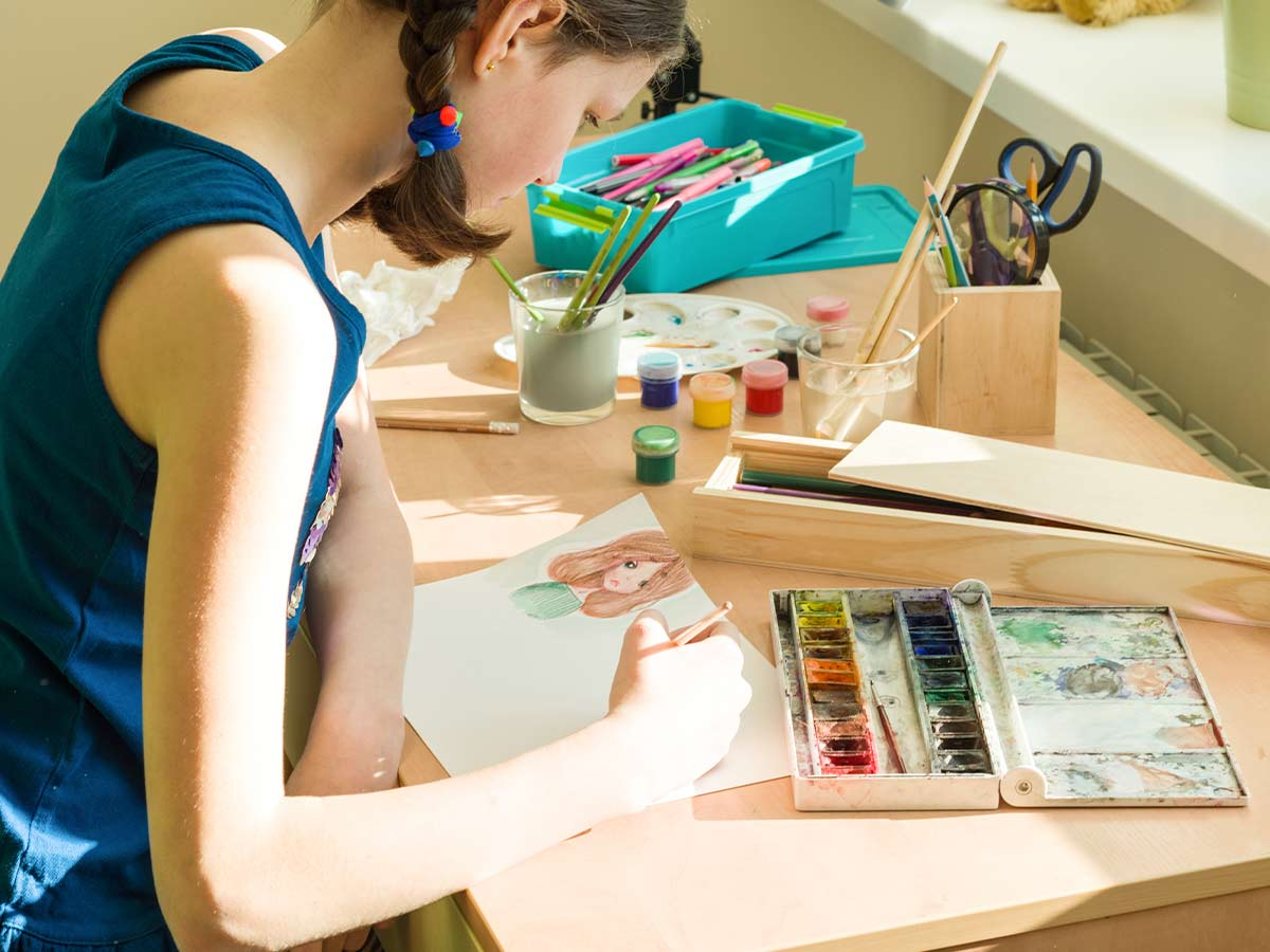 A teenage girl sits surrounded by art equipment, she is concentrating on completing a watercolour painting.