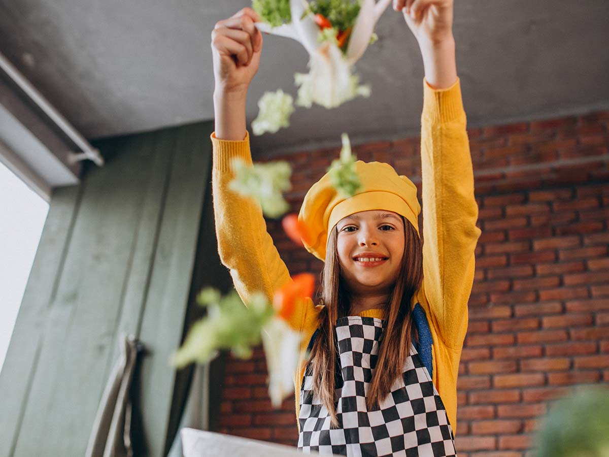 A tween girl wearing a chef's hat and apron tosses salad into the air whilst smiling at the camera.