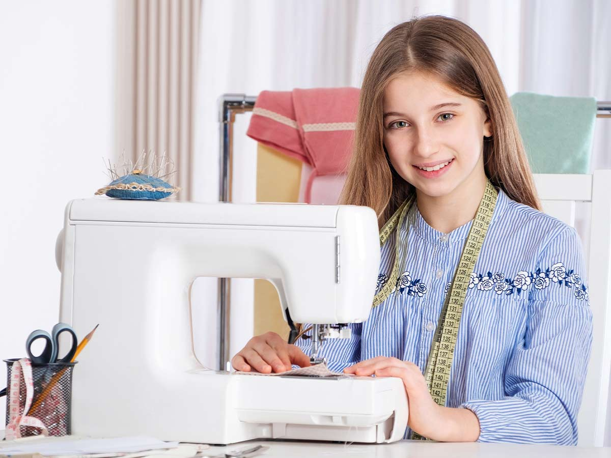 A tween girl sits at a desk in front of a sewing machine, she is surrounded by sewing equipment including a pin cushion and tape measure and is smiling at the camera.