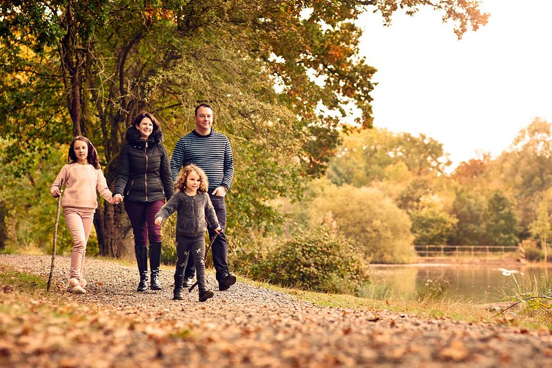 Family walking happily along nature trail with autumnal trees in the background, next to lake.