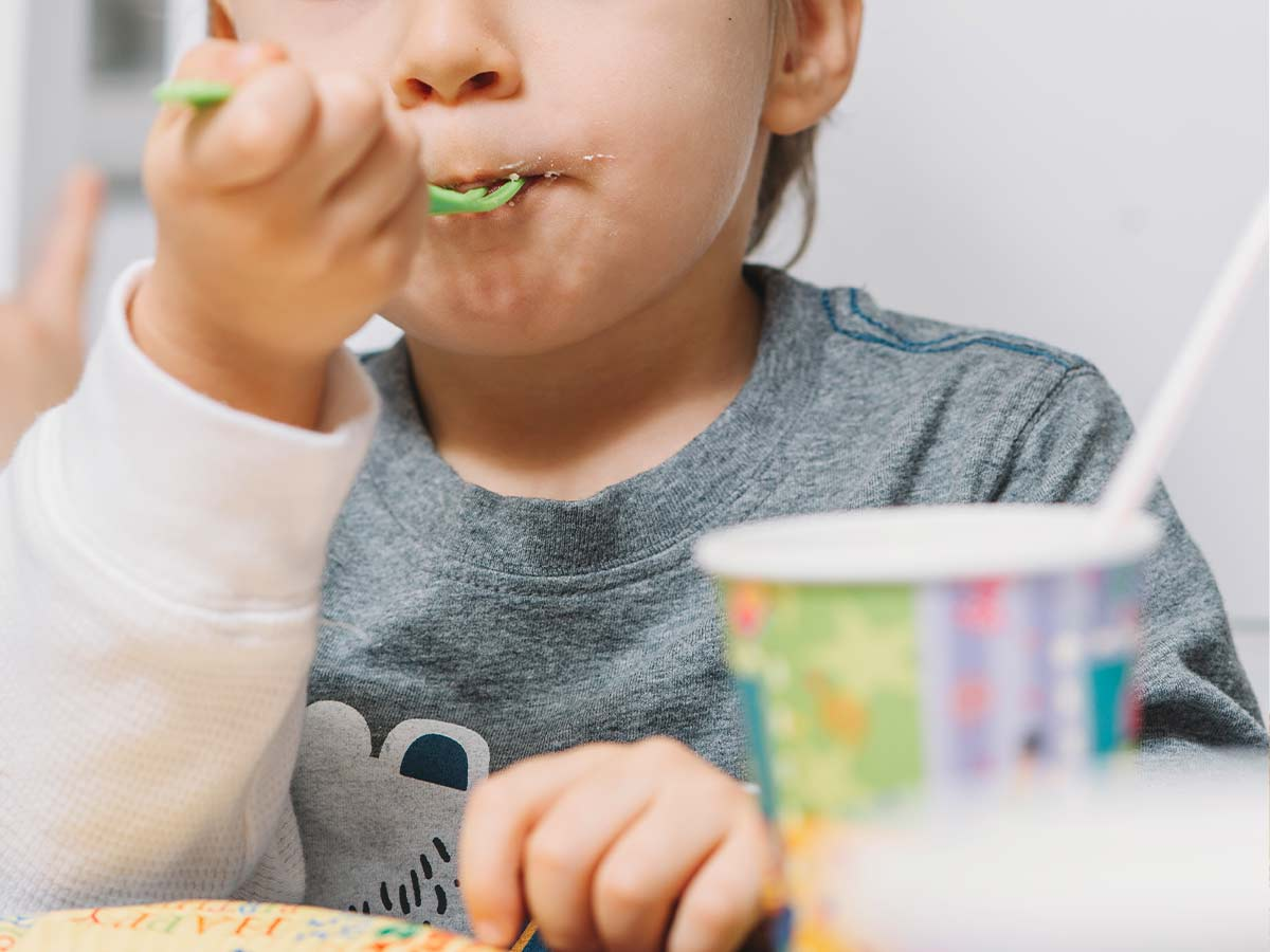 Close up of young boy eating a bite of Toy Story cake on a green plastic fork.