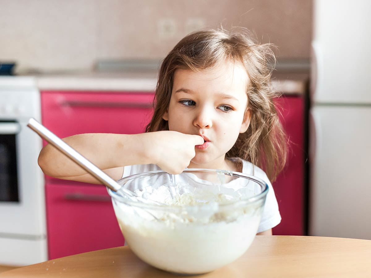 Little girl sneaks a taste of the ladybird cake mixture from the bowl.