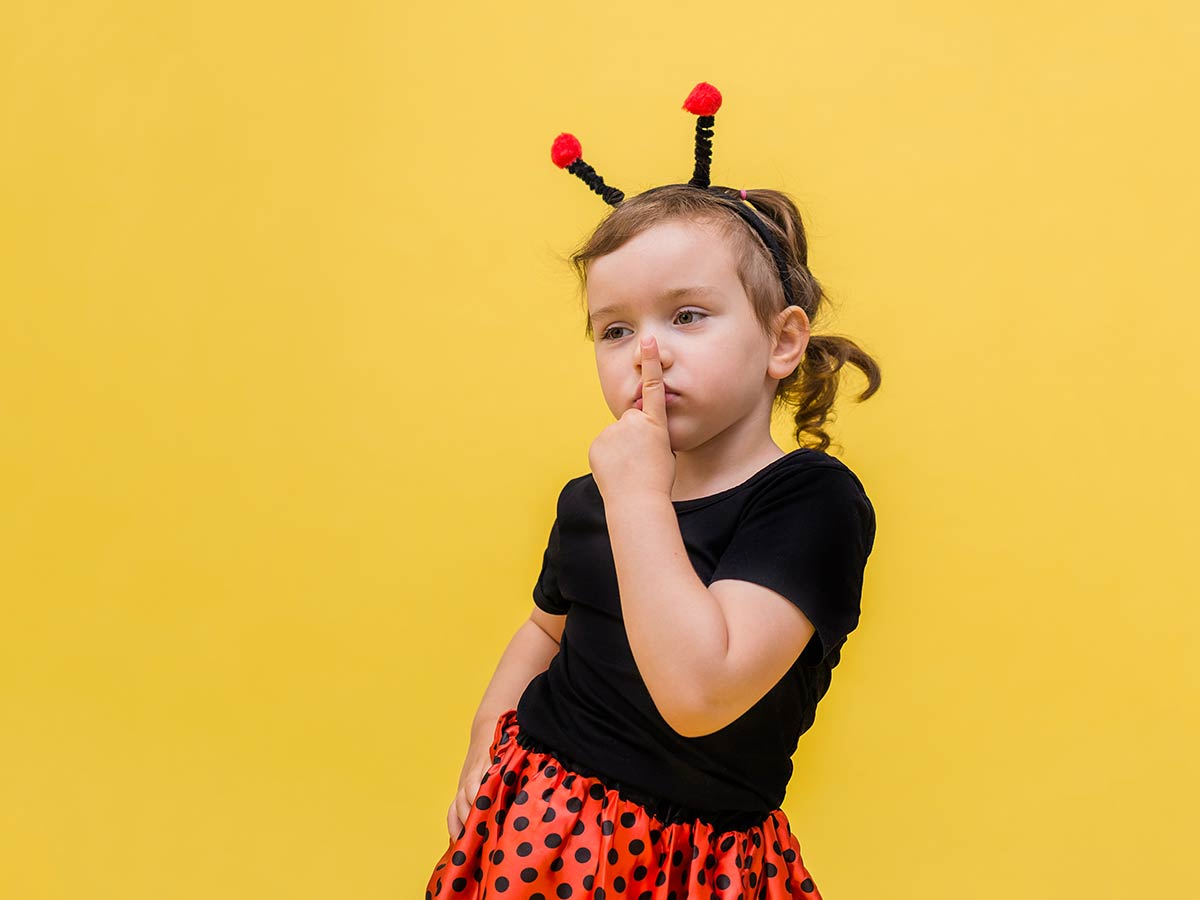 Little girl dressed as a ladybird poses for the camera against a yellow background.