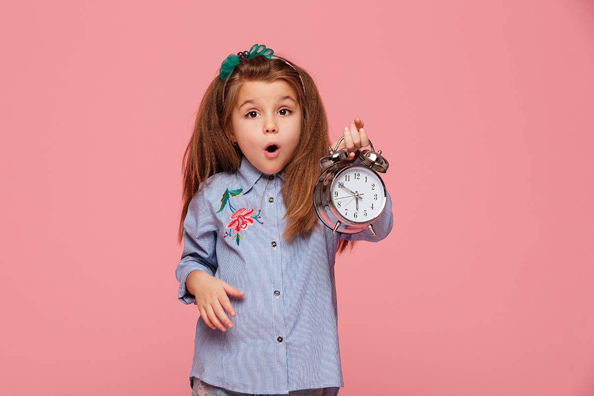 Little girl holding up a clock, learning to tell time.