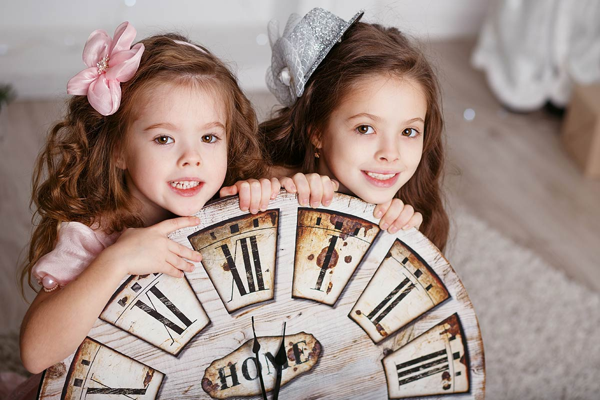 Two sisters crouching behind a large clock smiling.