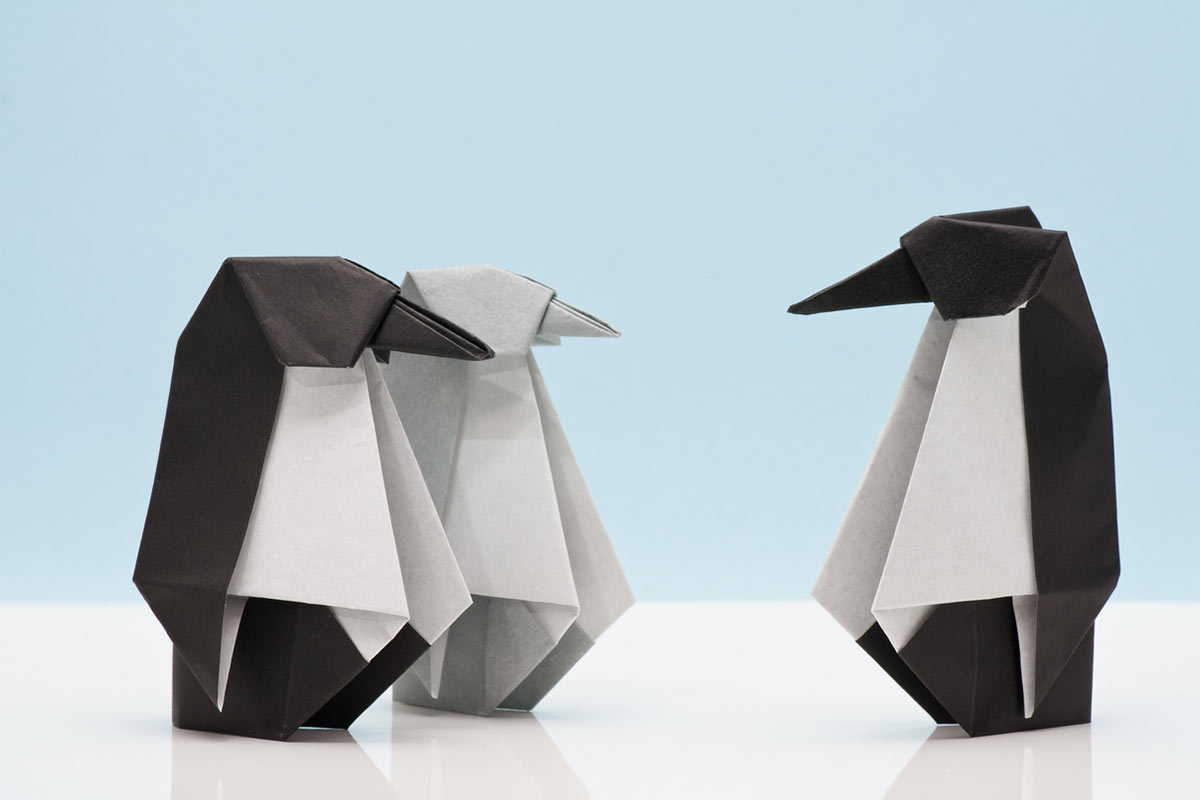 Three completed origami penguins, two are black and white and one is grey and white, standing against a blue background.