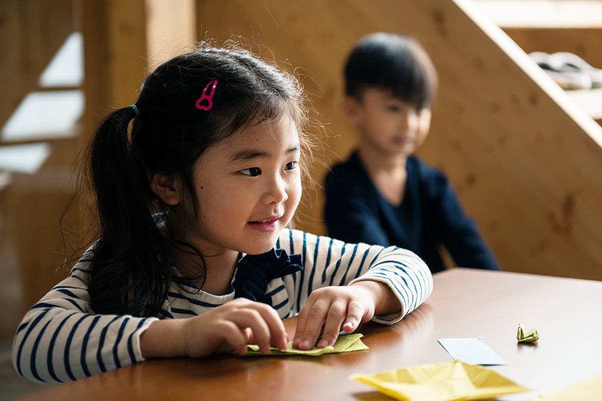 A little girl (and a boy in the background) are sat at a table folding an origami penguin.
