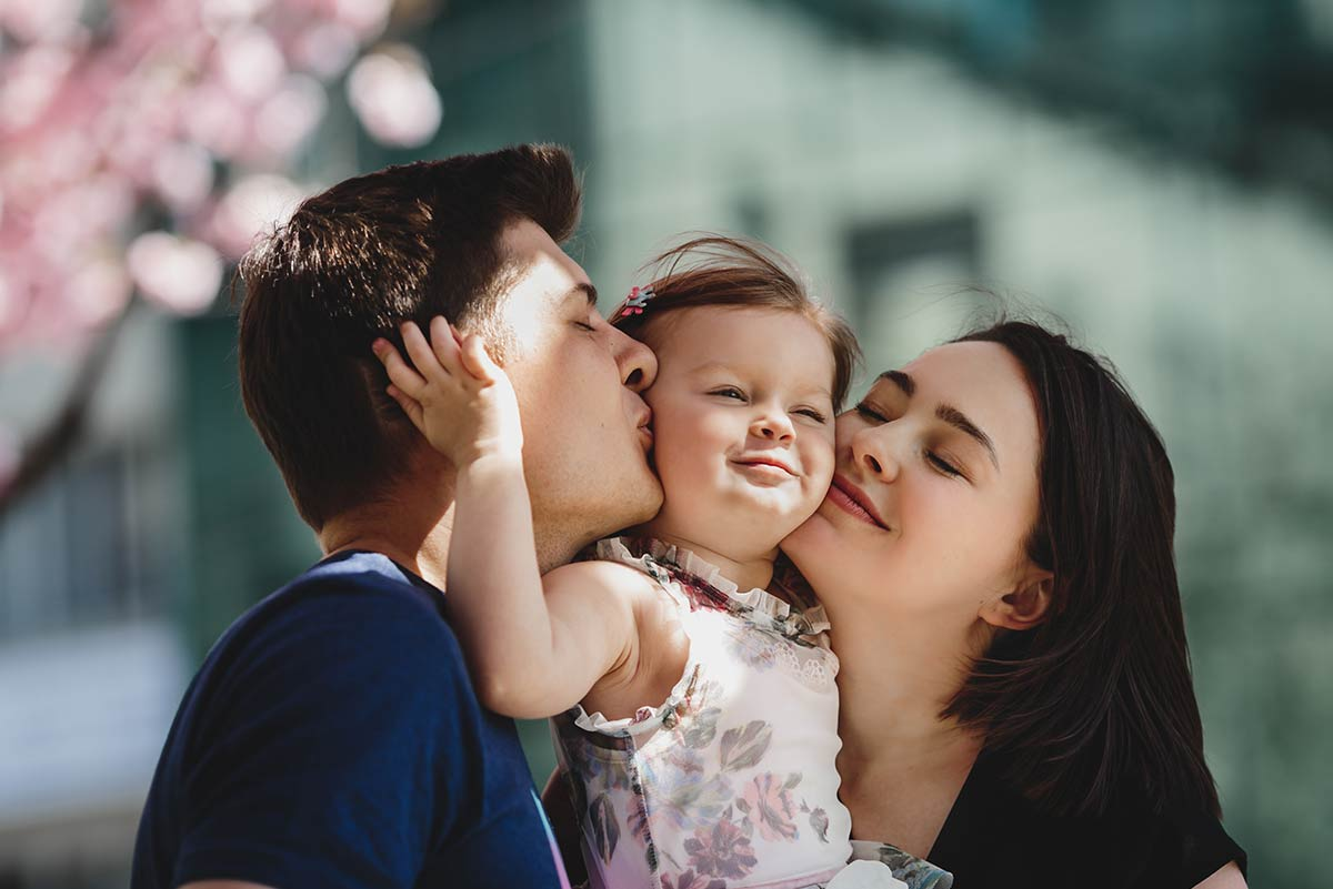 Parents holding their young daughter and kissing her on either cheek.