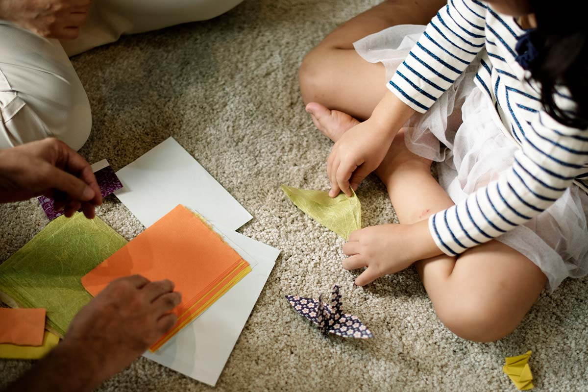 Overhead shot of a child and adult sitting on the floor folding paper to make an origami penguin.