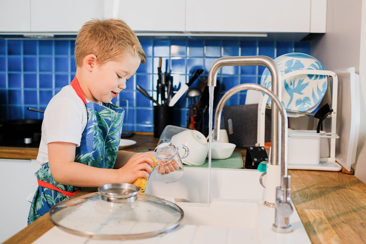 A young boy doing some washing up to earn a reward from his DIY reward chart.