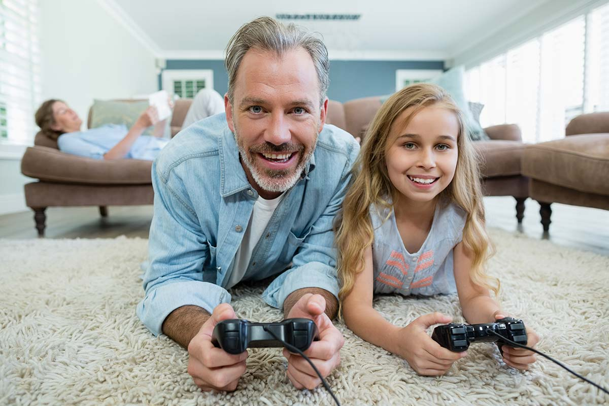 A girl and her father smile into the camera, they are enjoying her reward of playing a video game.