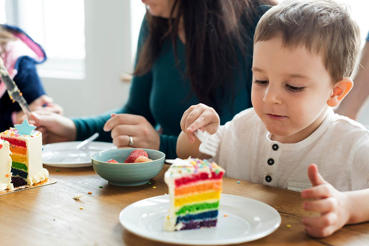 Young boy eating a slice of rainbow Power Ranger cake.