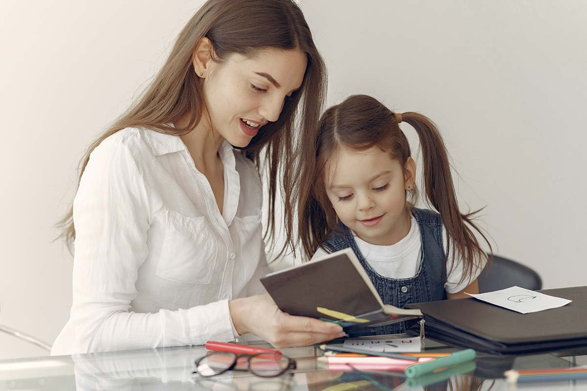 A mother and daughter sitting together looking in a notebook at her DIY reward chart.