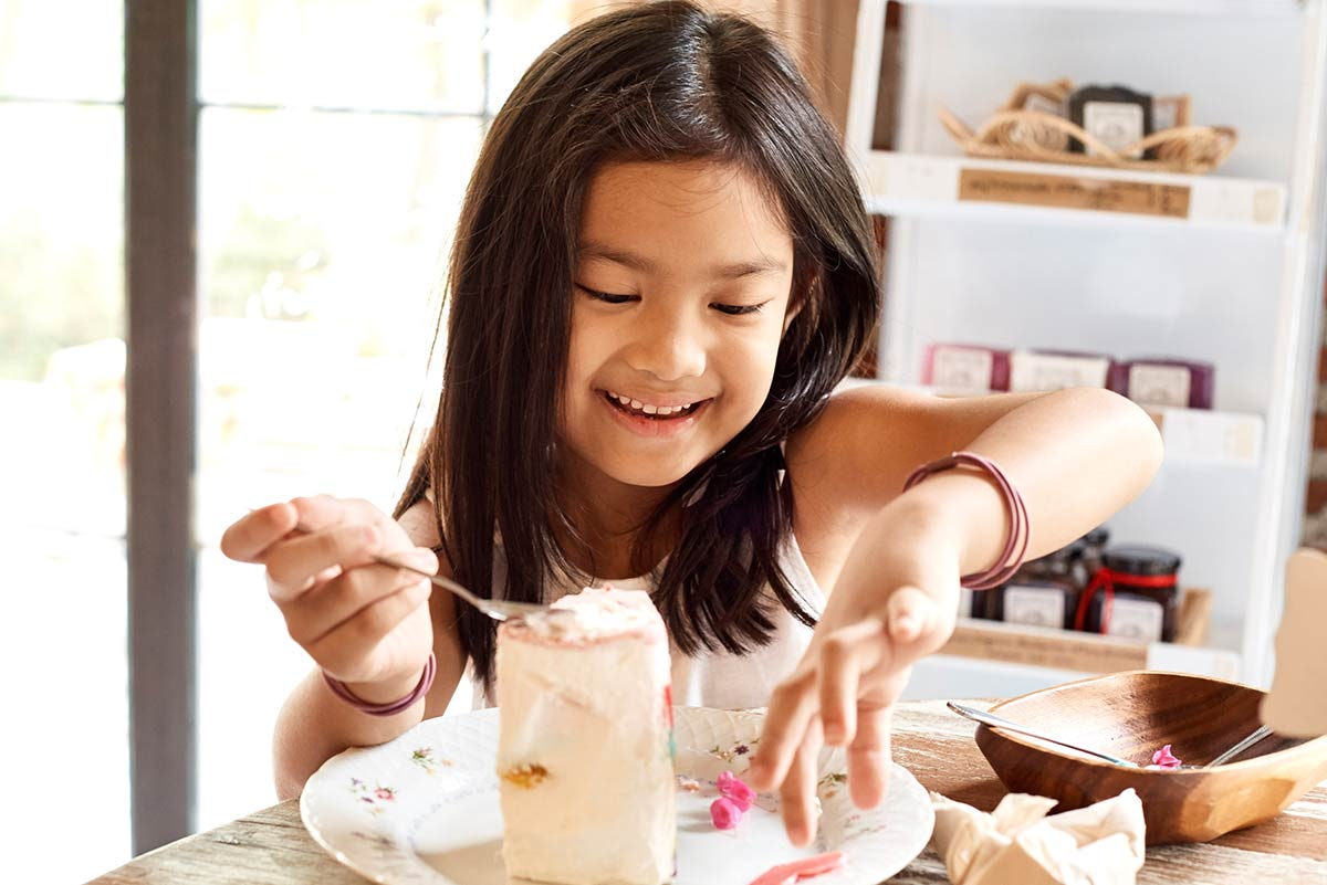 Young girl eating a large slice of birthday cake.