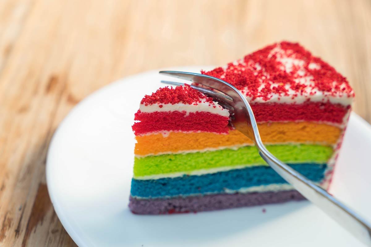 Fork slicing through a piece of rainbow Power Ranger cake.