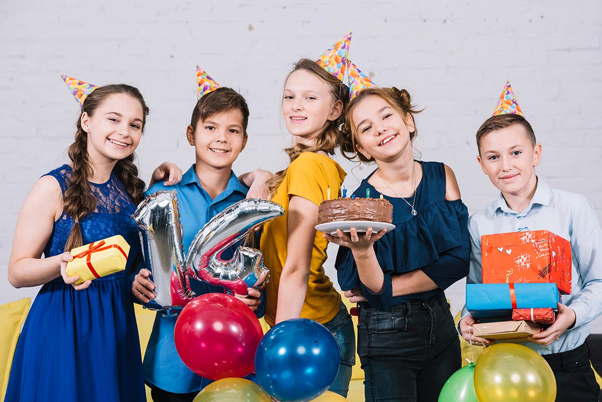 Group of teens wearing party hats and posing smiling at birthday party with a cake.