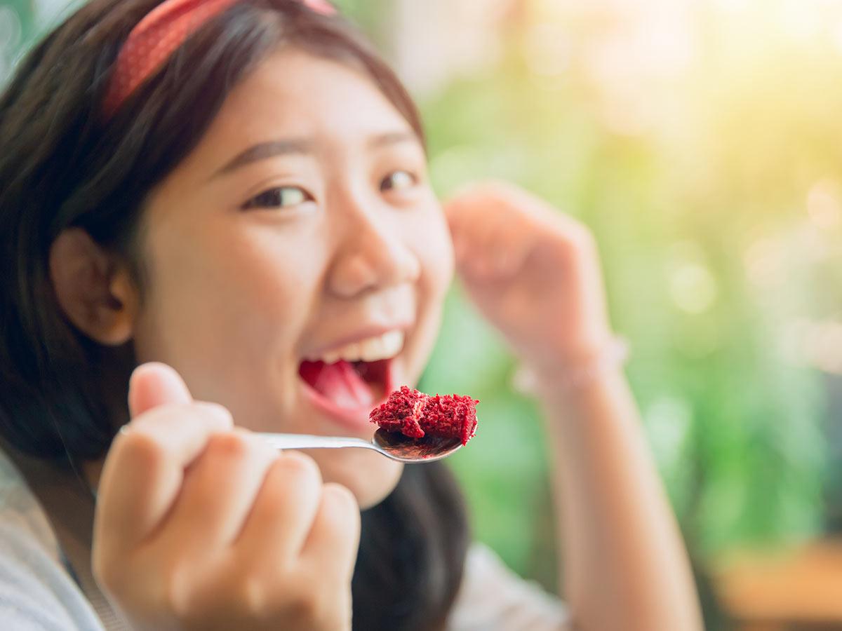 Teenage girl eating a bite of red velvet laptop cake.