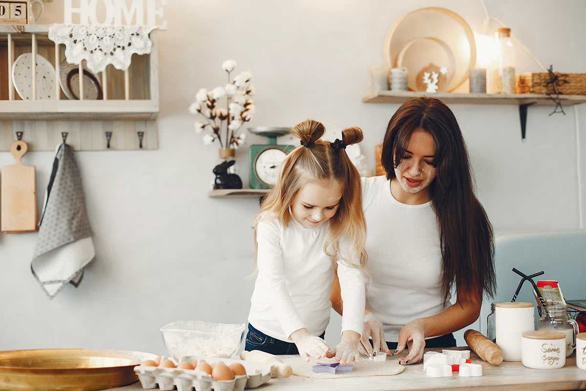 A mother and daughter are baking a gravity cake together in the kitchen.