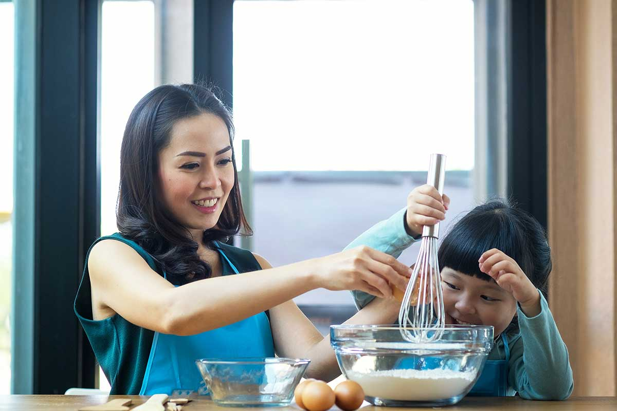 A mother and her child whisking ingredients together in the kitchen to make a gravity cake.