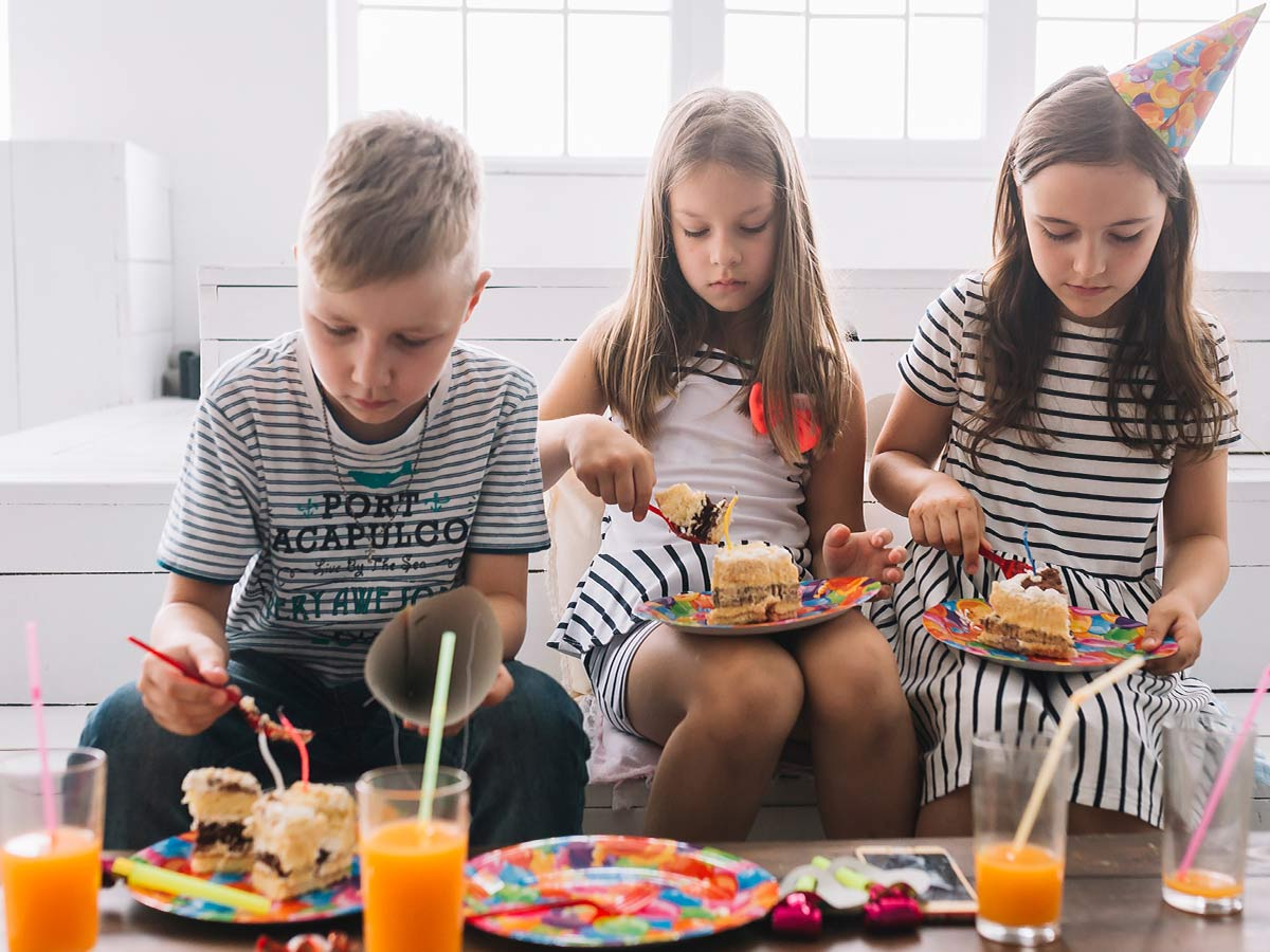 Three kids at a birthday party enjoying a slice of gravity cake, one child is wearing a colourful party hat.
