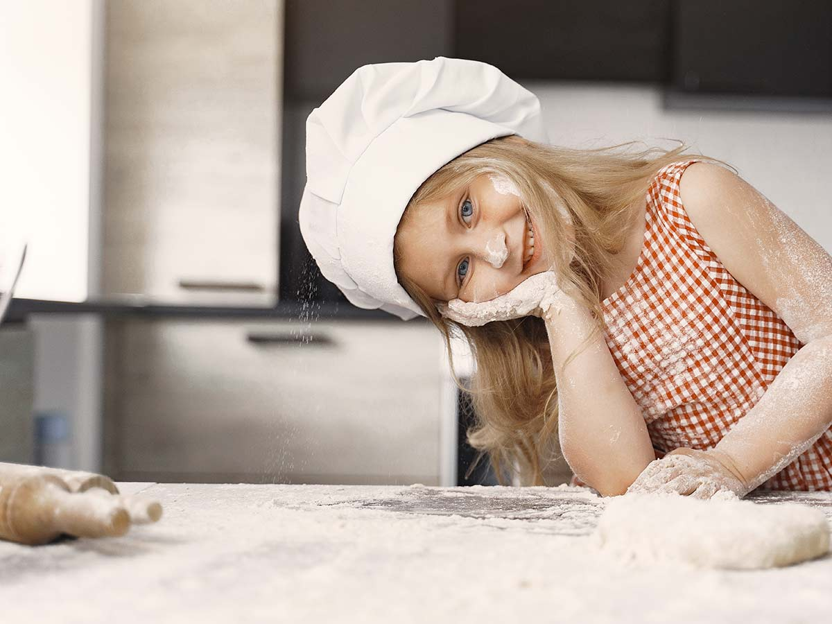 Young girl wearing a chef's hat smiling in the kitchen with flour on her face as she bakes a Scooby Doo cake.