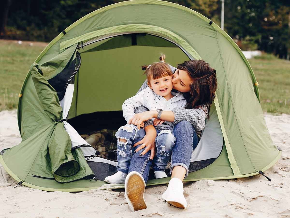 Mum kissing her toddler on the cheek while they sit in their tent on a camping holiday.