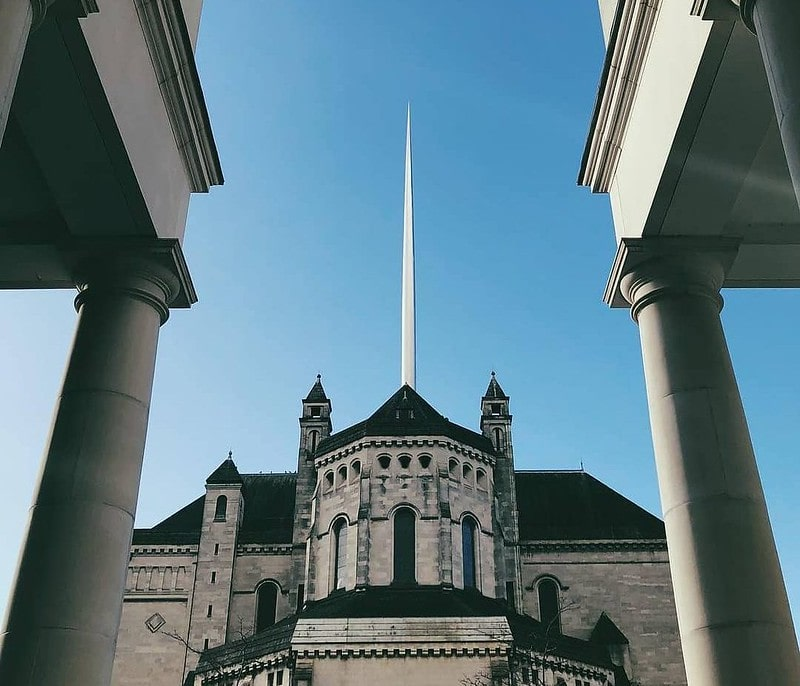 Exterior shot of Belfast Cathedral looking up at its tall spire on a sunny day.