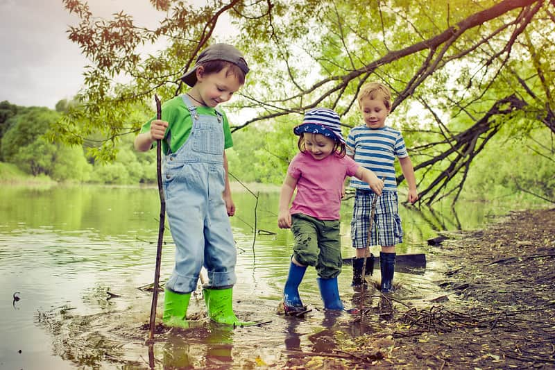 Three children on a camping trip playing in a pond.