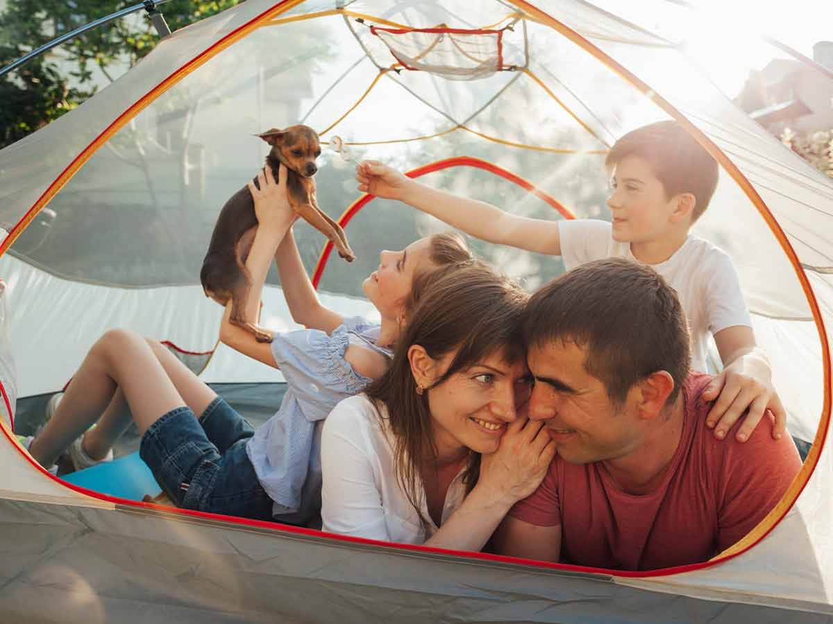 Happy family lying in their camping tent together with their dog.