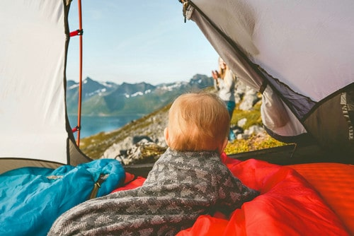 Toddler, wrapped in a blanket, lying on its tummy in the camping tent looking out the door at the view of mountains.