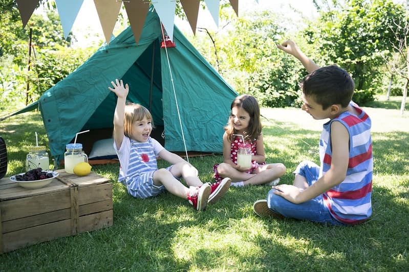 Three kids sat on the grass in front of their camping tent having fun and eating snacks.