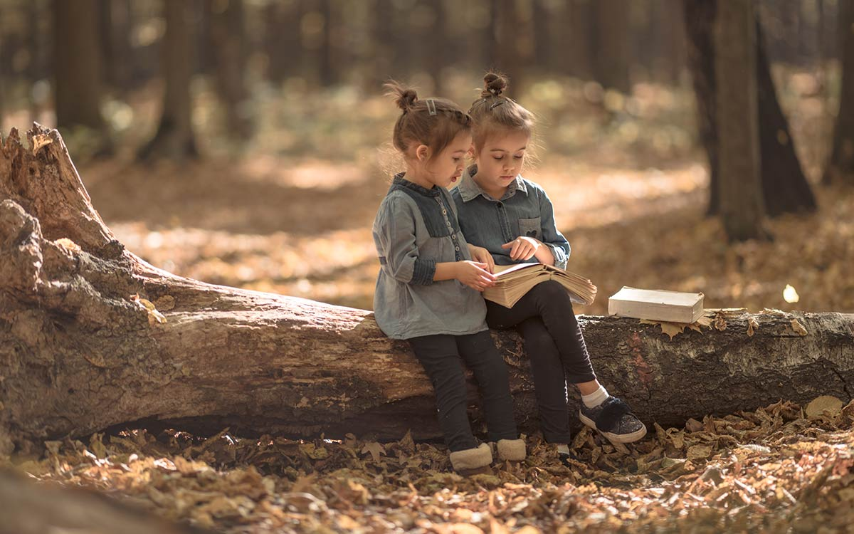Two little girls sat outside on a tree trunk reading a book together for their book review.