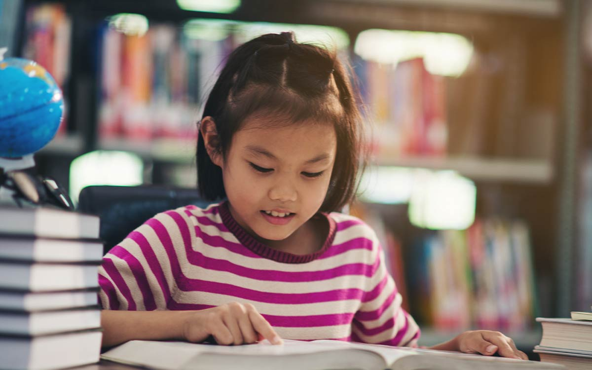 Little girl wearing a striped t shirt sat at a desk in the library reading a book for her book review.