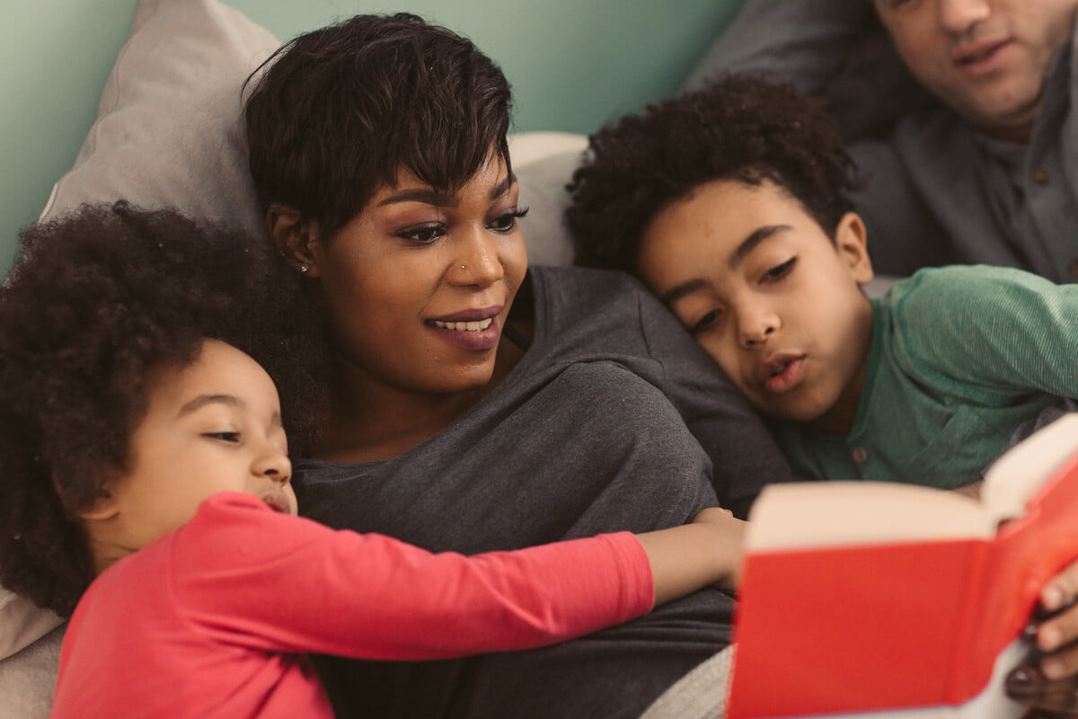 Family lying on the sofa, the mum reading with the two kids so that they can write a book review.