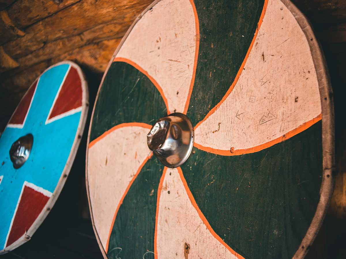 A close up image of two Viking shields, one is green and orange, the other is red with a blue cross.