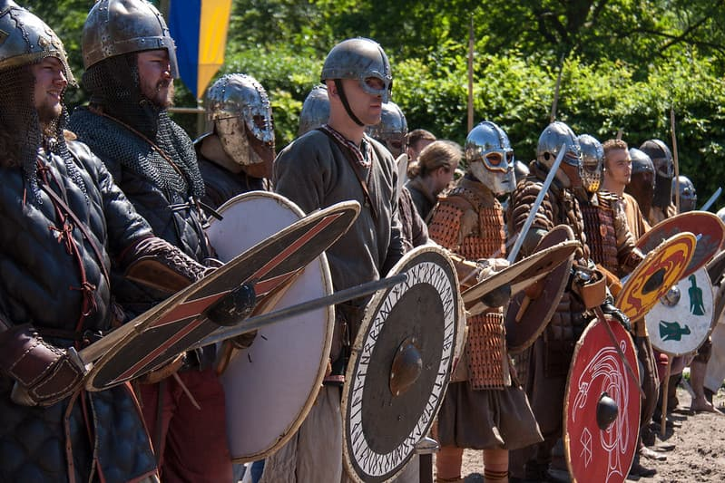 A Viking army dressed in armour and carrying swords and Viking shields.