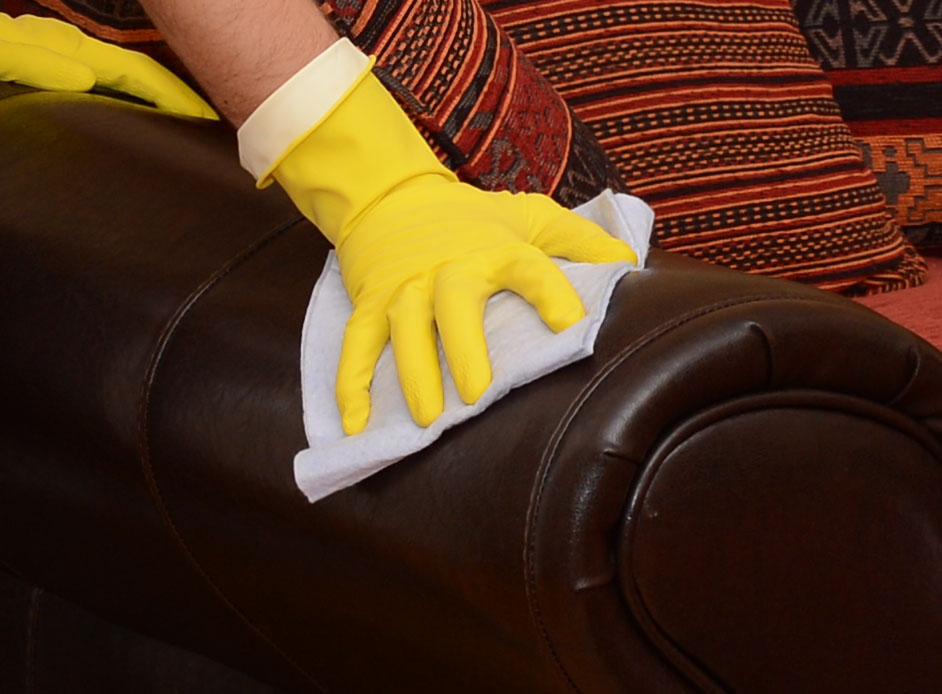 A close up image of a gloved hand rubbing a brown leather sofa with a cloth in an attempt to remove a biro stain.