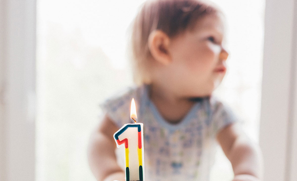 A toddler sits behind a cake with a colourful lit candle in the shape of the number one.