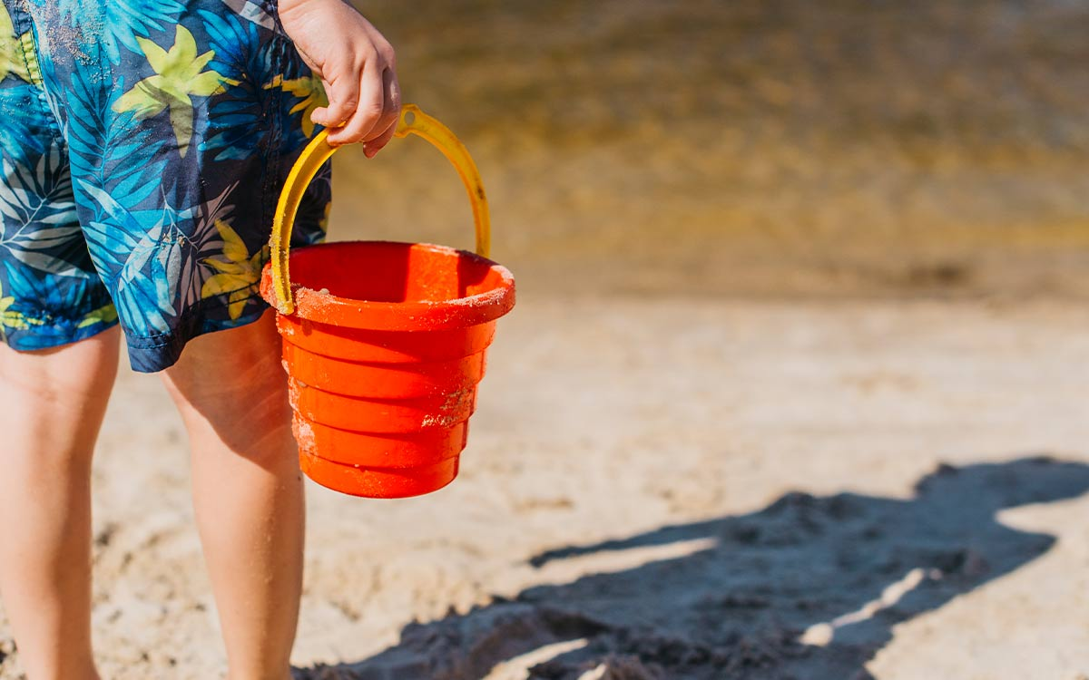 Boy standing on the beach holding a bucket, his shadow is in the sand in front of him.