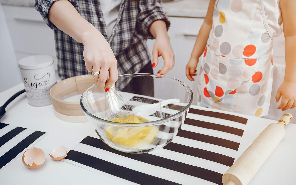 A close up image of an adult helping a child to whisk eggs in a bowl to make a superman cake.
