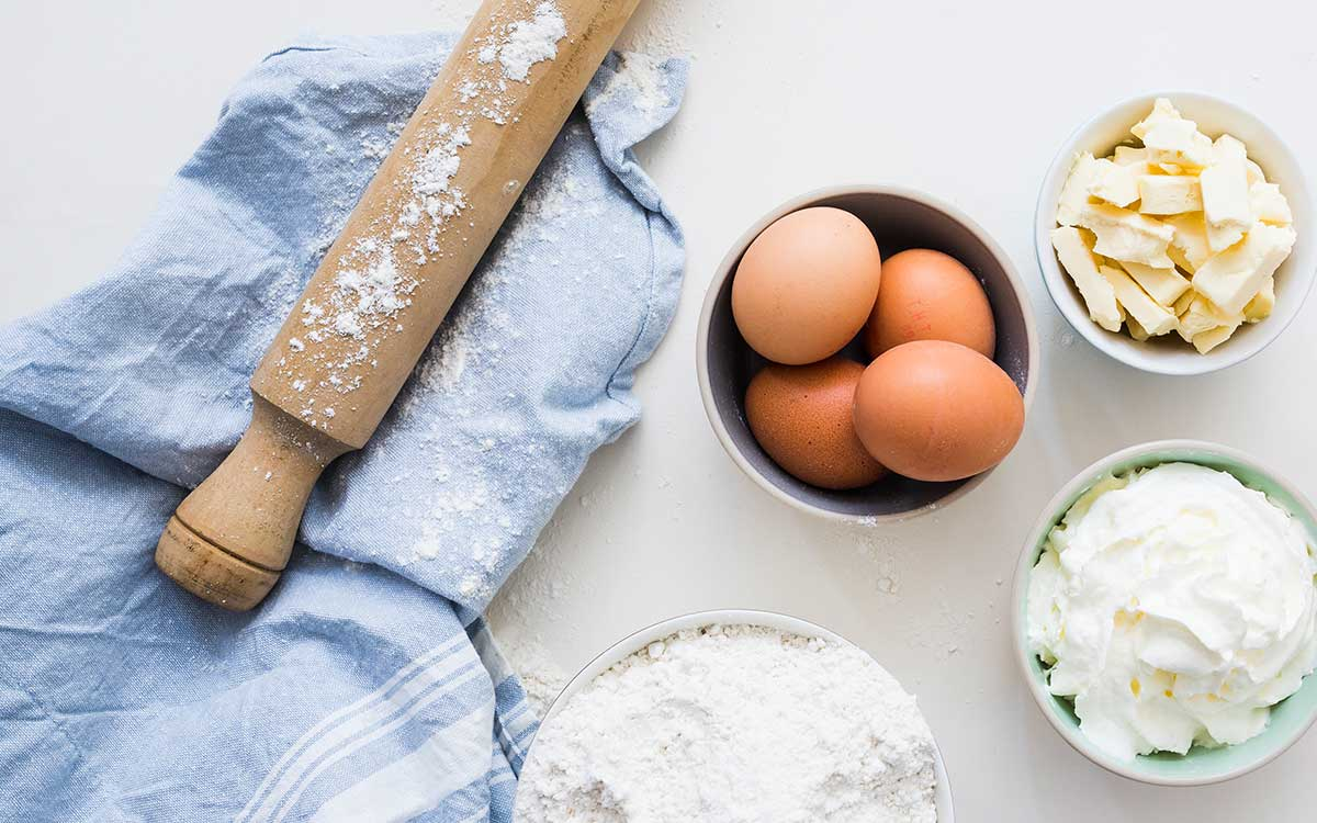 Some ingredients needed to make a superman cake, including eggs, butter and flour, are laid out on a white table with a rolling pin and a blue tea towel.