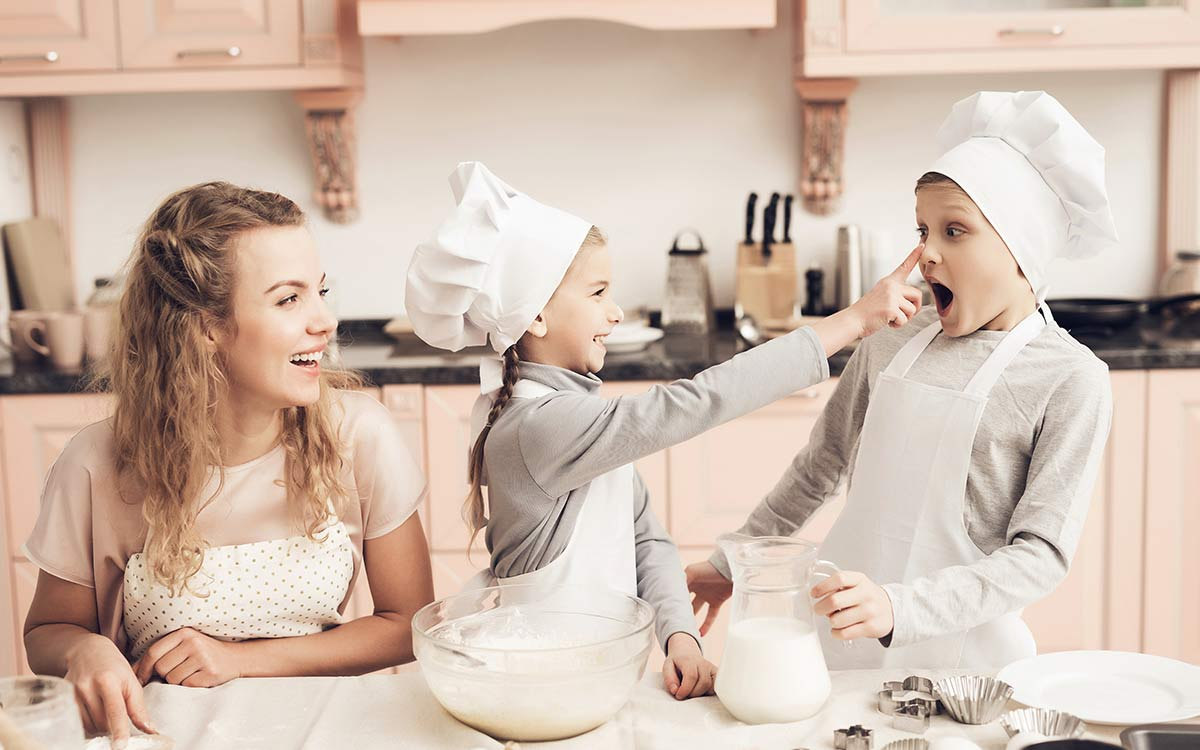 Three kids of different ages enjoy baking a burger cake together, two children are wearing white chef hats as they bake.