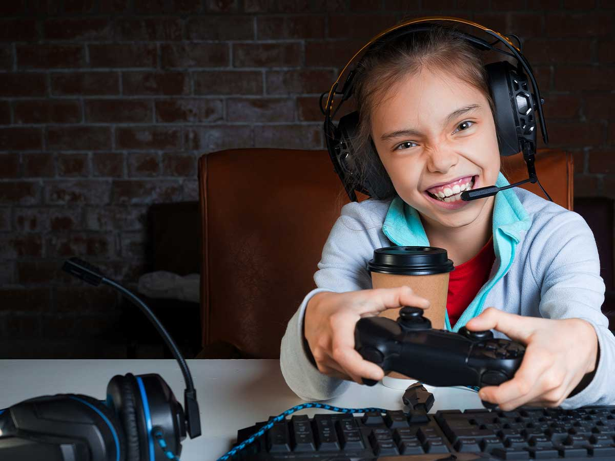 A young girl wearing headphones and holding a remote control smiles at the camera as she plays an Xbox game.