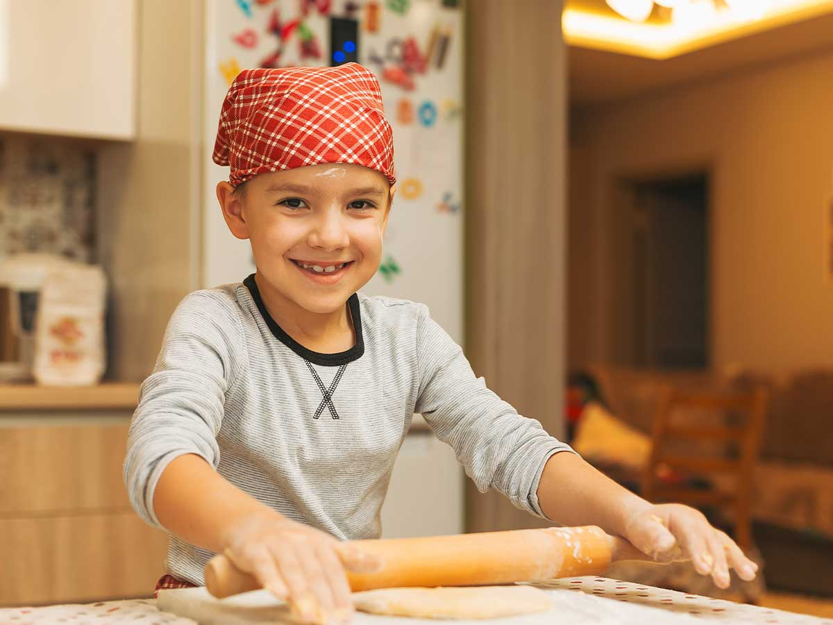 A young boy smiles at the camera as he uses a rolling pin to roll out fondant icing to decorate an Xbox cake.