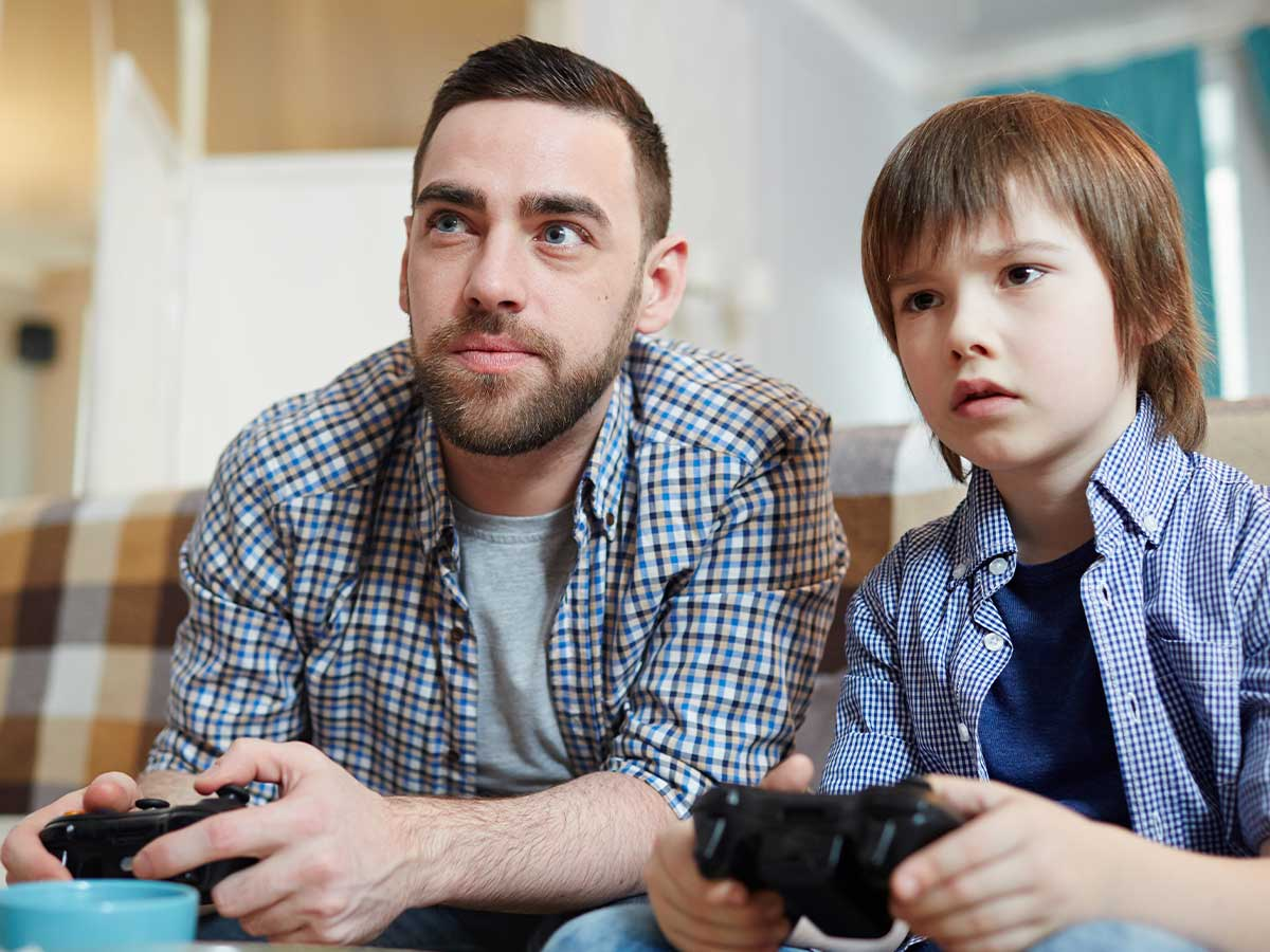 A father and son are sitting next to each other holding Xbox controllers, they both have a look of concentration on their face as they are playing an Xbox game.
